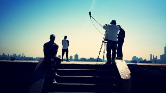 Early morning filming. This is a silhouette shot of cast and crew on set.
